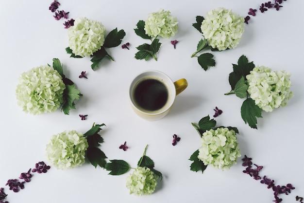 Grüne blumen und blumenblätter der flieder in form eines kreises, der um die gelbe schale mit kaffee auf weißem hintergrund liegt Premium Fotos