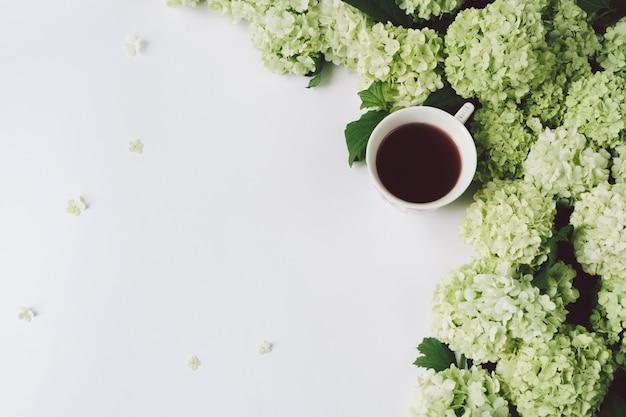Grüne blumen und gelbe schale mit tee auf einem weißen hintergrund Premium Fotos