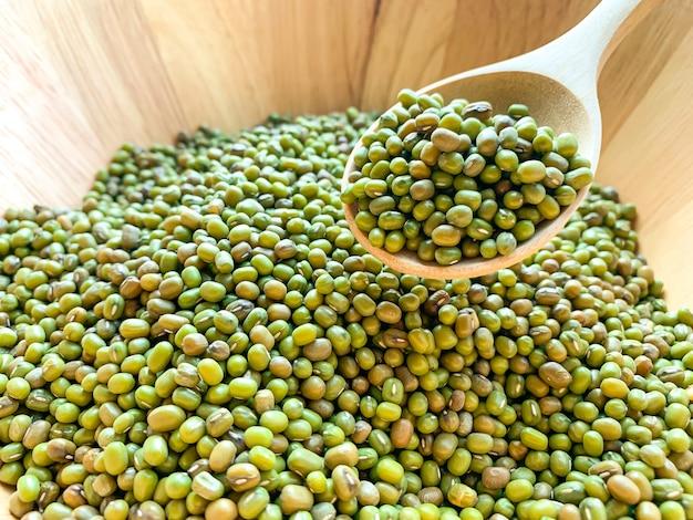 Grüne bohnen auf einem holzlöffel in einer holzschale Premium Fotos