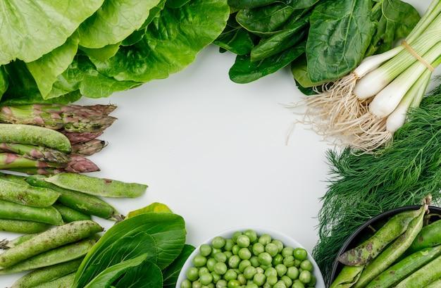 Grüne erbsen, schoten in schüssel und topf mit spinat, sauerampfer, dill, salat, spargel und frühlingszwiebeln lagen flach auf einer weißen wand Kostenlose Fotos