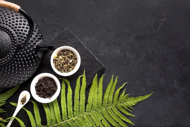Grüne farnblätter und getrocknetes teekraut mit schwarzer teekanne auf schwarzem hintergrund Kostenlose Fotos