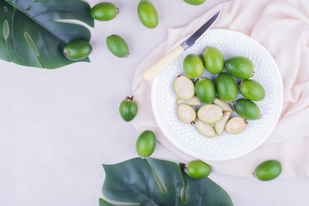 Grüne feijoas in einem weißen teller mit blättern herum Kostenlose Fotos