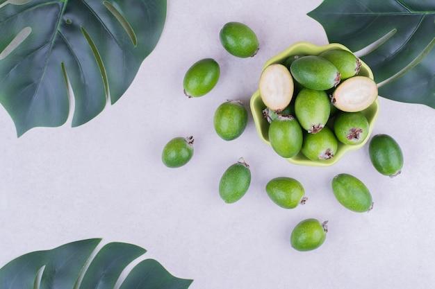 Grüne feijoas in einer grünen tasse mit blättern herum Kostenlose Fotos