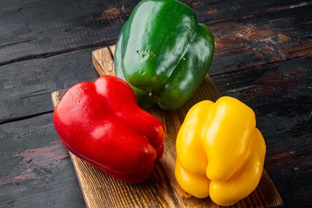 Grüne, gelbe und rote paprika auf altem dunklem holztisch Premium Fotos