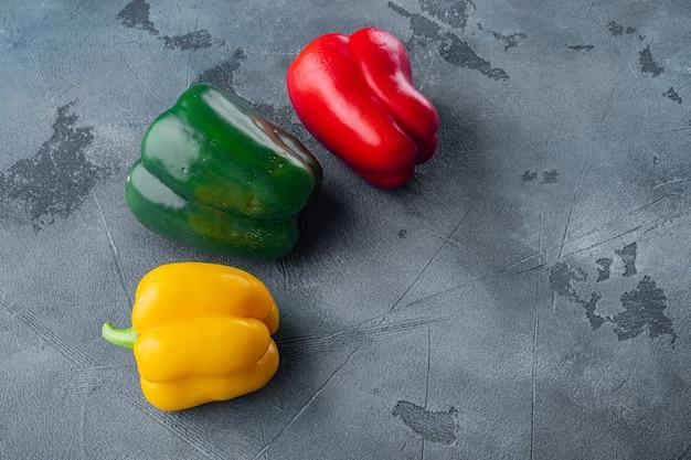 Grüne, gelbe und rote paprika auf grauem tisch Premium Fotos