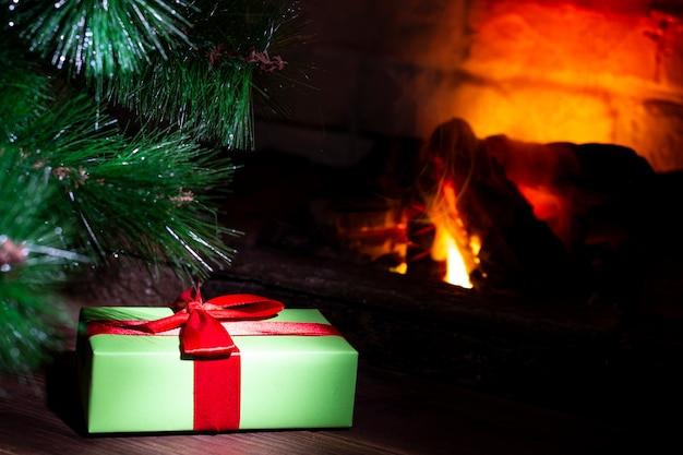 Grüne geschenkbox mit einem roten bogen unter dem weihnachtsbaum auf einem holztisch nahe einem biokamin Premium Fotos