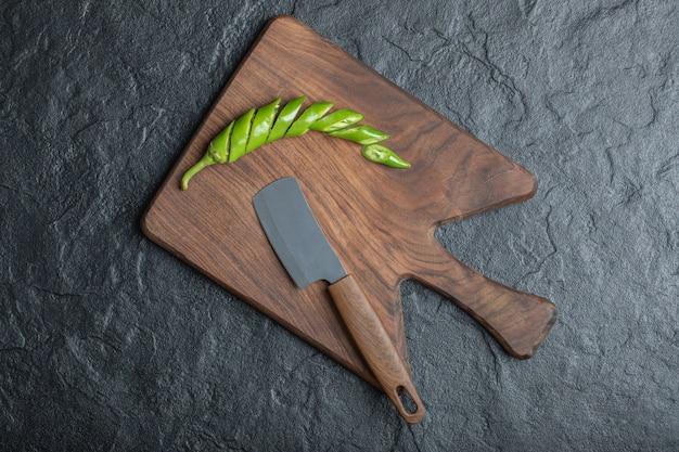 Grüne geschnittene scharfe chilischote auf holzschneidebrett. hochwertiges foto Kostenlose Fotos