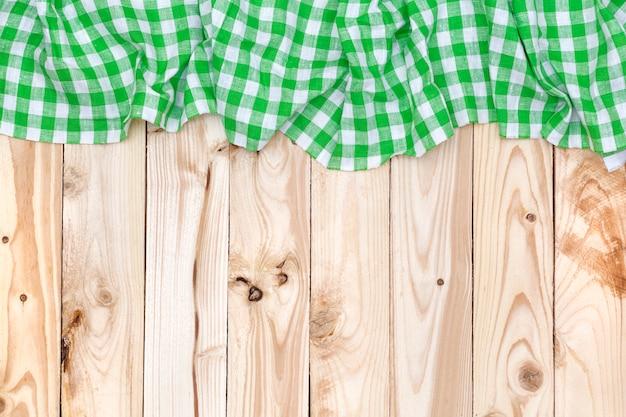 Grüne karierte tischdecke auf holztisch, draufsicht Premium Fotos