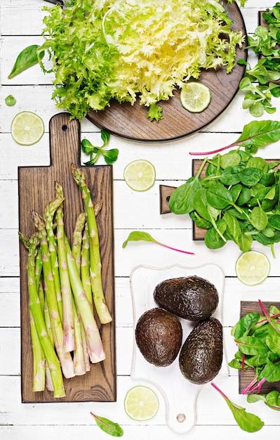 Grüne kräuter, spargel und schwarze avocado auf einem weißen hölzernen hintergrund. ansicht von oben. flach liegen Kostenlose Fotos