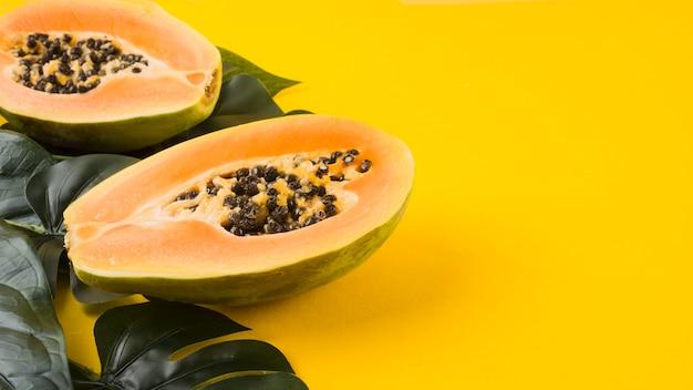 Grüne künstliche blätter mit halbierter papayafrucht auf gelbem hintergrund Premium Fotos