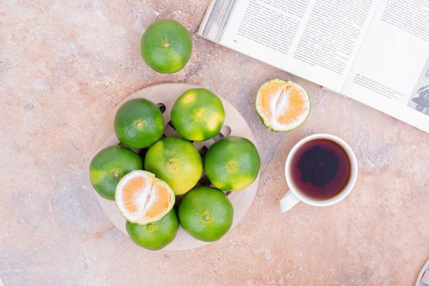 Grüne mandarinen mit einer tasse tee. Kostenlose Fotos