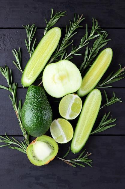 Grüne obst, gemüse und rosmarin auf schwarzen brettern mit kopienraum. avocado, kalk, kiwi und grüner apfel auf hölzernen brettern. draufsicht der gurken- und rosmarinniederlassungen. gesundes essen Premium Fotos