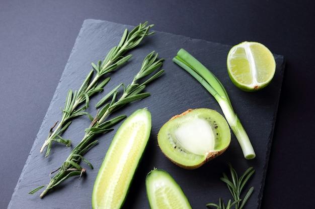 Grüne obst und gemüse auf dunklem schieferbrett. konzept der natürlichen grünen produkte. avocado, kiwi, kalk und apfel auf dunklem hintergrund. rosmarin, dill und schnittlauch auf steinplatte Premium Fotos