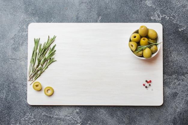 Grüne oliven in schalen und rosmarin zweige auf einem weißen brett Premium Fotos