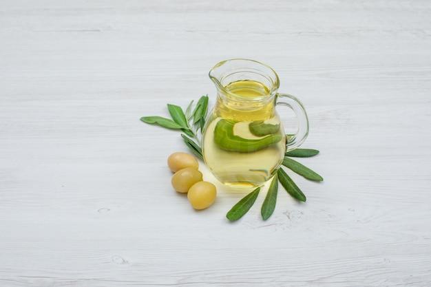 Grüne oliven und olivenöl in einem glas mit seitenansicht der olivenblätter auf weißem holzbrett Kostenlose Fotos