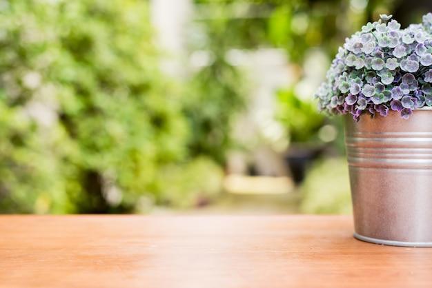 Grüne pflanze in einem blumentopf auf einem hölzernen schreibtisch an der vor dem haus mit verschwommenen garten blick strukturierten hintergrund. Kostenlose Fotos