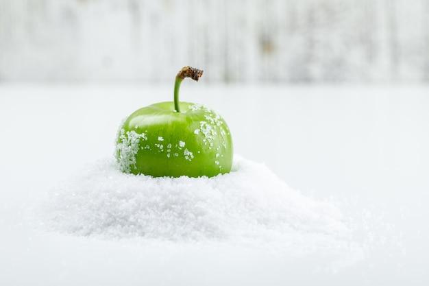 Grüne pflaume mit salzkristallen auf weißer und schmuddeliger wand, seitenansicht. Kostenlose Fotos
