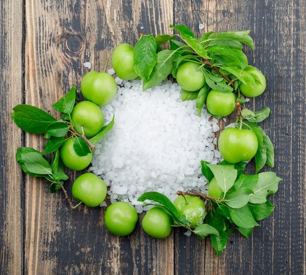 Grüne pflaumen mit salzkristallen, blätter an holzwand, flach gelegen. Kostenlose Fotos