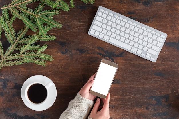 Grüne tannenbaumaste des winters mit tasse tee, handy und weißer computertastatur auf hölzernem Premium Fotos