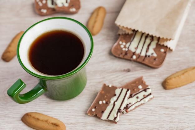 Grüne tasse americano und milchschokolade Premium Fotos