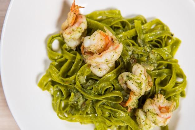 Grüne teigwaren mit garnelen und käse in der weißen platte auf hellem holztisch in einem restaurant Premium Fotos