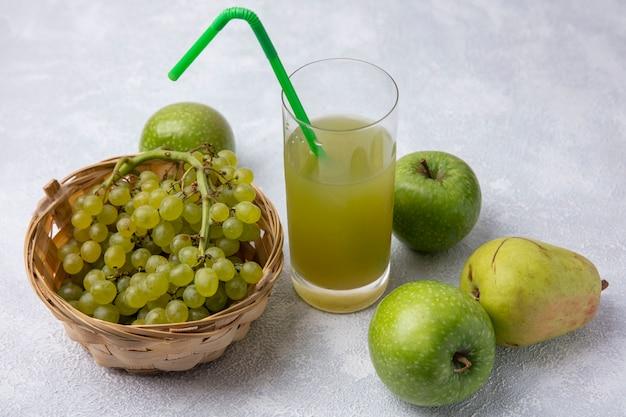 Grüne trauben der seitenansicht in einem korb mit birnengrünen äpfeln und apfelsaft mit einem grünen strohhalm in einem glas auf einem weißen hintergrund Kostenlose Fotos