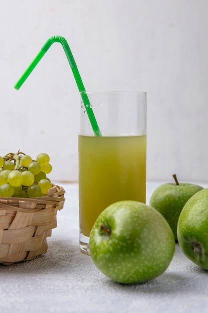 Grüne trauben der vorderansicht in einem korb mit birnengrünen äpfeln und apfelsaft mit einem grünen strohhalm in einem glas auf einem weißen hintergrund Kostenlose Fotos