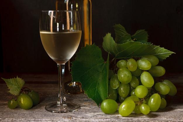 Grüne trauben mit blättern, glas, flasche weißwein Premium Fotos