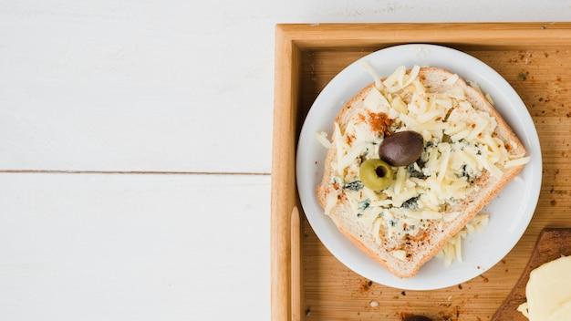 Grüne und rote oliven mit geriebenem käse auf brot über der platte im behälter Kostenlose Fotos