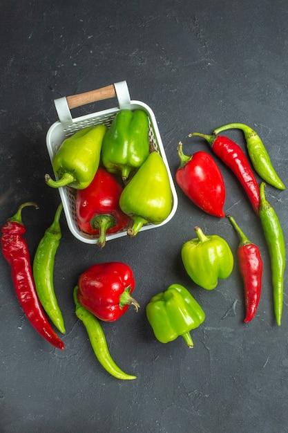 Grüne und rote paprika von oben in plastikkorb-peperoni auf dunkler oberfläche Kostenlose Fotos
