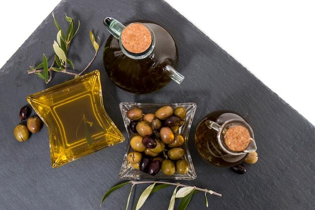 Grüne und schwarze oliven mit olivenölflaschen Premium Fotos