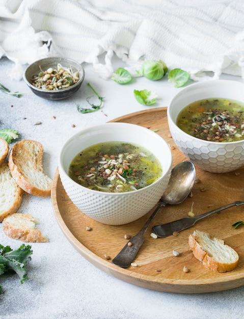 Grüne vegane gemüsesuppe von keil, rosenkohl, zucchini, lauch mit verschiedenen gekeimten samen und sprossen mit croutons auf holztablett Premium Fotos