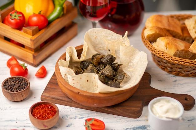 Grüne weinblätter gefüllt mit fleisch, reis, kräutern, zwiebeln und gekochtem olivenöl, serviert mit lavash und brot. yarpag dolmasi, yaprak sarmasi Kostenlose Fotos