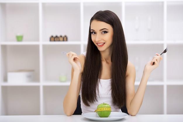 Grüner apfel auf einem weißen teller, gabel, messer, gewichtsverlust, gesunde ernährung, gelbes maßband, gewichtsverlust Premium Fotos