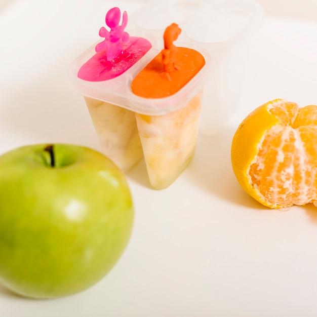 Grüner apfel; orange und eis am stiel schimmel auf dem schreibtisch Kostenlose Fotos