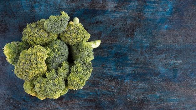 Grüner brokkoli zerstreut auf blaue tabelle Kostenlose Fotos