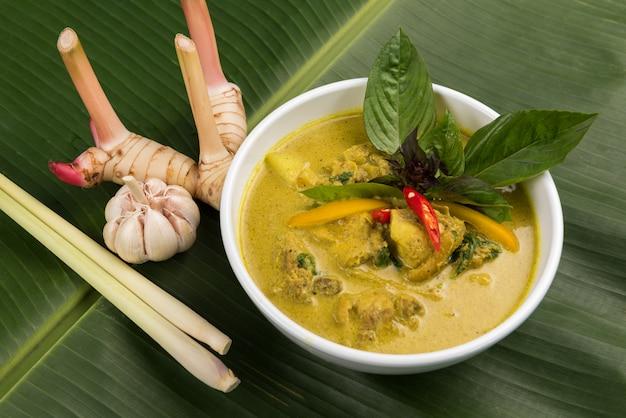 Grüner curry mit huhn in der schüssel mit galangal- und zitronengras auf bananenblatt Premium Fotos