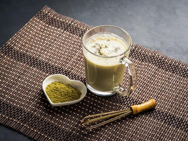 Grüner matcha tee lattebecher auf dunkelheit Premium Fotos