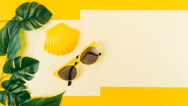 Grüner monstera verlässt mit sonnenbrille und kamm-muschel auf papier gegen gelben hintergrund Kostenlose Fotos