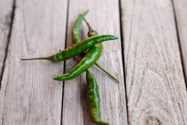 Grüner roher chili auf holzoberfläche Premium Fotos