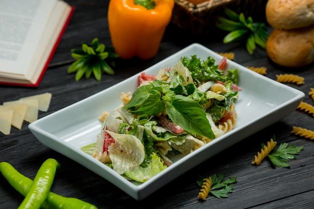 Grüner salat mit frischen tadellosen blättern und gehacktem parmesankäse in einer quadratischen platte. Kostenlose Fotos