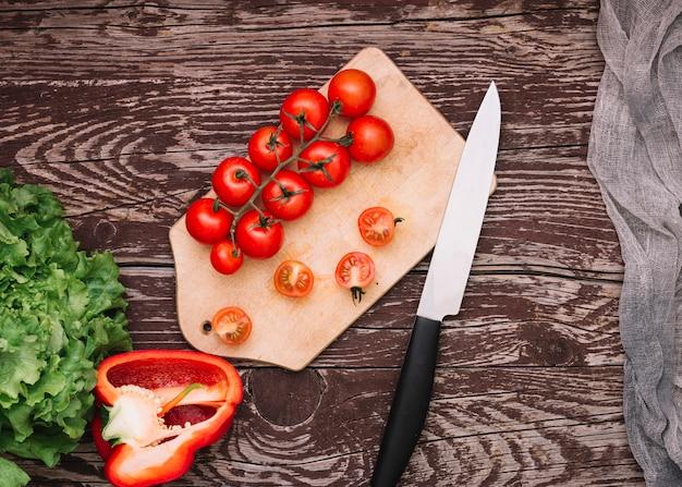 Grüner salat; paprika- und kirschtomaten auf schneidebrett mit messer über dem holzschreibtisch Kostenlose Fotos