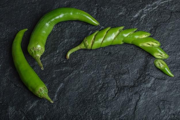 Grüner scharfer chili-pfeffer geschnitten oder ganz auf schwarzem hintergrund. hochwertiges foto Kostenlose Fotos