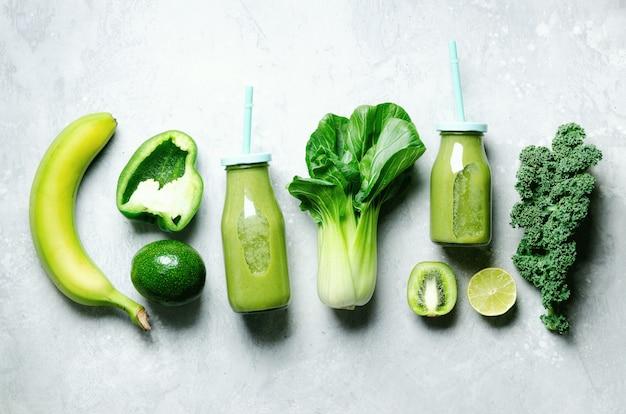 Grüner smoothie im glasgefäß mit frischem organischem grünem gemüse und früchten auf grau. Premium Fotos
