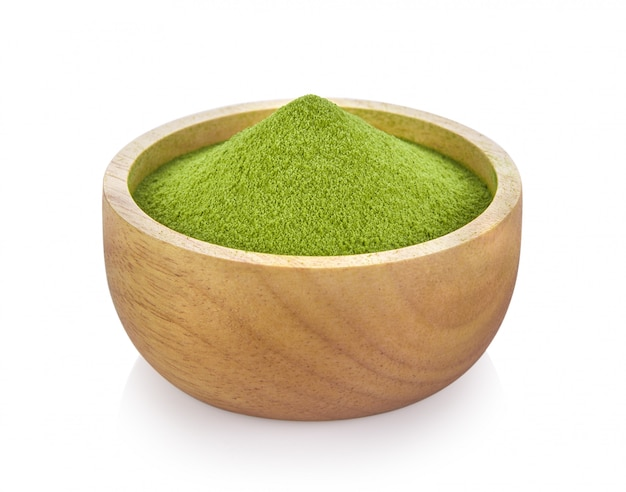 Grüner teepulver in der holzschale auf weißem raum Premium Fotos