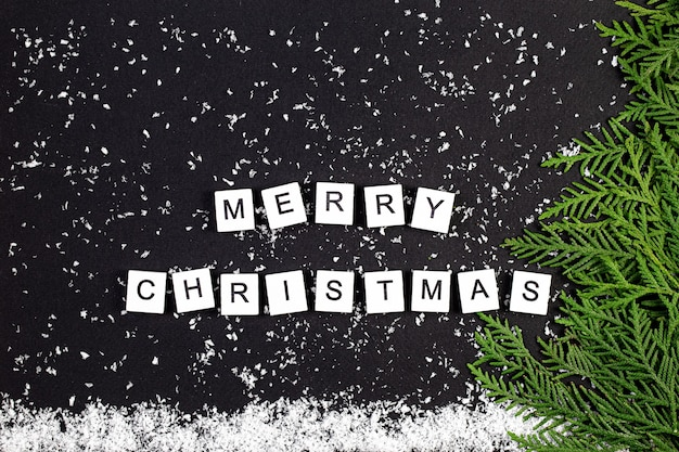 Grüner weihnachtsbaum gemacht von nadelbaumzweigen und schneeflocken auf einem dunklen hintergrund. minimaler kompositionshintergrund. neujahrs- und weihnachtskonzept. Premium Fotos