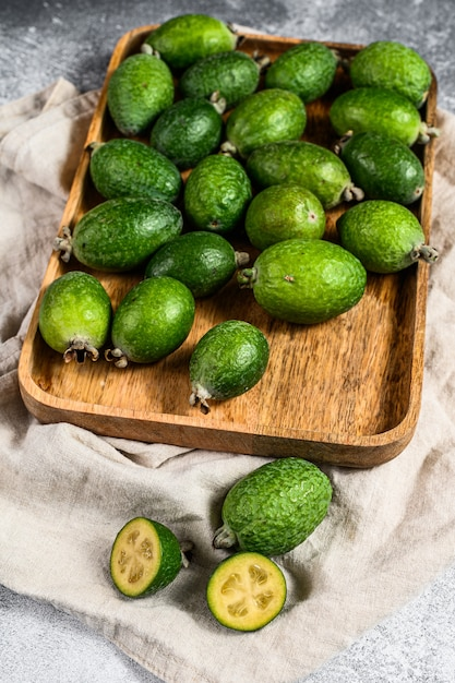 Grünes feijoa trägt in einer hölzernen platte auf einem grauen hintergrund früchte. tropische früchte feijoa. ansicht von oben Premium Fotos