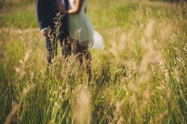Grünes gras auf dem gebiet an einem sonnigen sommertag, im unscharfen kerl und im mädchen, jungvermählten. Premium Fotos