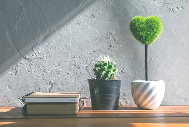Grünes herz, buchkaktusblume auf hölzernem tabellen-, liebes- und valentinstagkonzepthintergrund, hintergrund. Premium Fotos