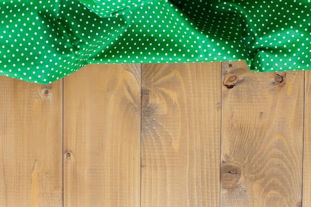 Grünes küchentuch auf einer hölzernen arbeitsplatte, küchenartikel, textilien. Premium Fotos